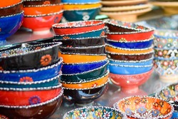 Colorful Glass bowls and saucers kept on display as a souvenir. These artistic hand made designer bowls are used as home decor items