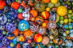 colorful Glass marbles of different sizes in a color pattern as methaphor for multicultural community diversity
