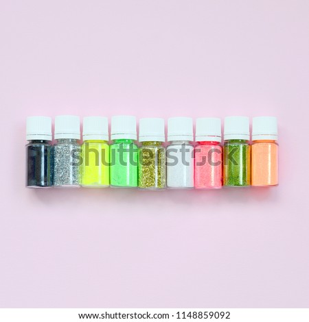 Colorful glitters lies on pastel pink background. Many round jars with multi-colored bright sparkles for nail polish. Sparkling sequins #1148859092