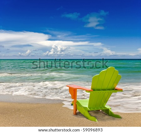 Colorful green and orange lounge chair at the tropical beach in Miami Florida with beautiful ocean waters and blue sky.