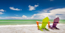 Colorful green and purple  lounge chair at the tropical beach in Miami Florida with beautiful ocean waters and blue sky.
