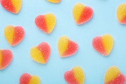 Colorful gummy candies pattern on blue background. Jelly sweets in shape of heart. Top view - Image