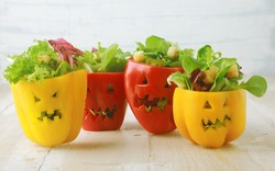Colorful Halloween food background with colorful healthy stuffed red and yellow sweet bell peppers with cutout faces in the skin like Halloween jack-o-lanterns filled with green salad and cheese