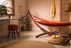 Colorful hammock with pillow in modern room interior