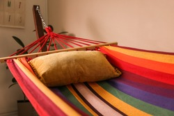 Colorful hammock with soft pillow indoors, closeup