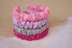 Colorful handmade headband made out of satin silk fabric texture. The hairband or headpiece with ruffle pattern is called scrunchy or scrunchies headband.