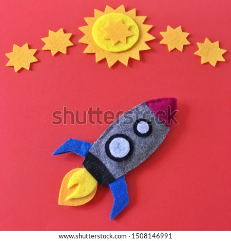 Colorful handmade rocket ship crafted with felt fabric. Yellow stars on red background with rocketship toy to DIY. Crafting supplies for hand made baby crib mobile for nursery. Happy colorful image. #1508146991