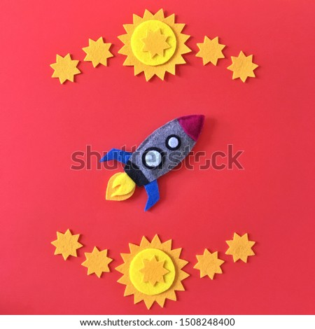 Colorful handmade rocket ship crafted with felt fabric. Yellow stars on red background with rocketship toy to DIY. Crafting supplies for hand made baby crib mobile for nursery. Happy colorful image. #1508248400