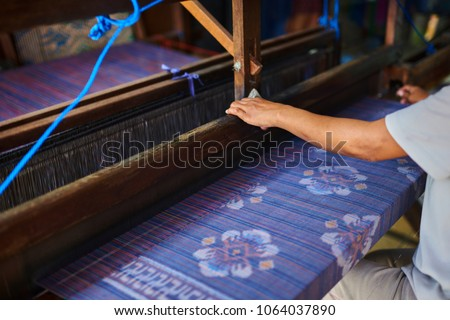 Colorful handmade sarong or saree made of cotton and silk. Ethnic clothing of Indonesian woman. Weaving and manufacturing of handmade fabric. Women's hands make cloth on the loom. Selective focus.