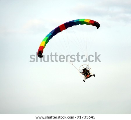 Colorful hang glider in blue sky