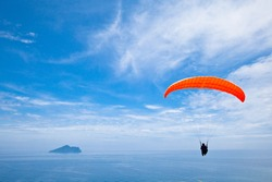 Colorful hang glider in blue sky over  sea