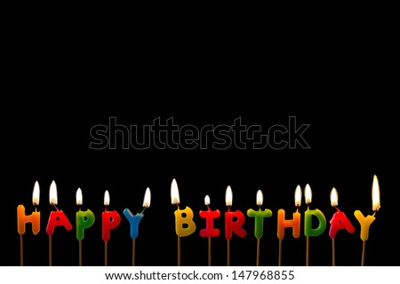 Colorful happy birthday candles on black background