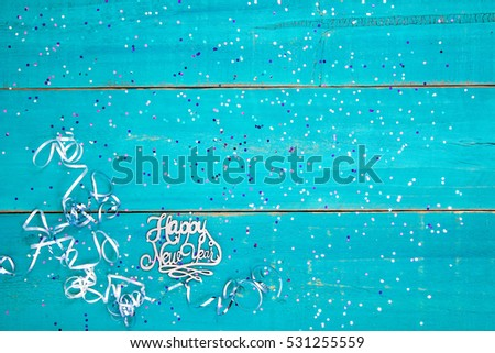colorful happy new year sign with holiday confetti and ribbon border on blank antique rustic teal