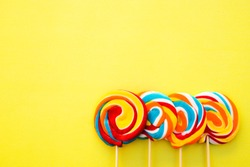 Colorful hard candy lollipop on yellow pastel background. Rainbow sweet pattern on stick flying around. Christmas holiday design concept elements.
