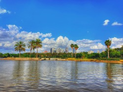 Colorful HDR image of the Yarkon Park with its famous park lake and the skyscrapers of Tel Aviv and Ramat Gan on a beautiful cloudy sky