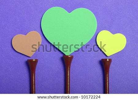 Colorful hearts set on golf tees with color background