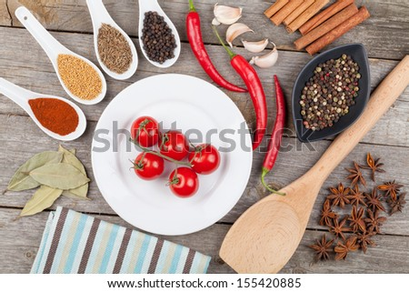 Colorful herbs and spices selection. Aromatic ingredients on wood table and cherry tomatoes on plate
