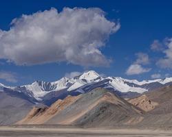 Colorful high altitude desert landscape with snow capped mountain range along Pamir Highway between Karakul and Kyzyl Art pass, Murghab, Gorno-Badakshan, Tajikistan