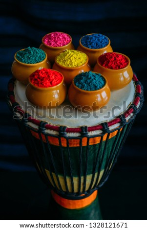 Colorful Holi powder in cups closeup standing on Indian drum djembe. Bright colours for Indian holi festival in clay pots. Selective focus.  Selective focus #1328121671