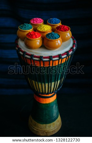 Colorful Holi powder in cups closeup standing on Indian drum djembe. Bright colours for Indian holi festival in clay pots. Selective focus.  Selective focus #1328122730