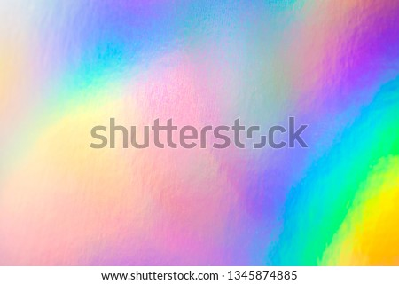 Photo of  colorful holographic paper with rainbow lights.