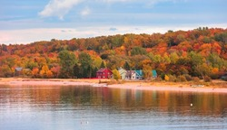 Colorful homes at the Lake Superior shore surrounded by Fall foliage in Michigan
