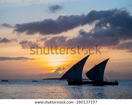 Colorful horizontal photo of silhouettes of two traditional Tanzanian dhow boats on open sea on Indian Ocean close to Stone Town on Zanzibar island, Tanzania in East Africa, at orange sunset.