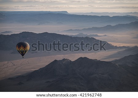 Colorful hot air ballon flying over the mountain landscape. High altitude. Early morning, High dark mountains. (Namibia, South Africa)