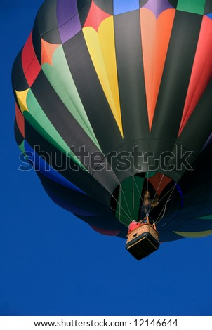 Colorful hot air balloon ascending into blue sky