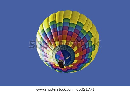 Colorful hot air balloon floats in a clear blue sky.