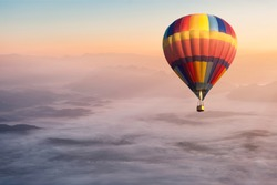 Colorful hot air balloon flying in the air with fog and scenery mountains in morning