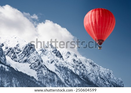 Colorful hot-air balloon flying over snowcapped mountain