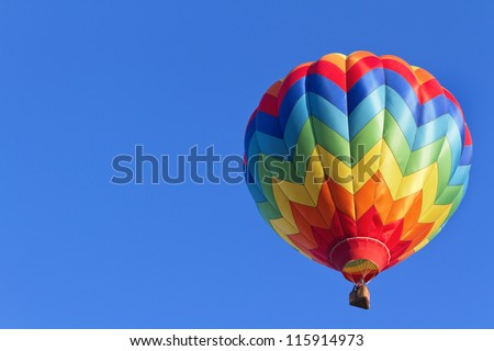 Colorful hot air balloon moving up in blue sky.