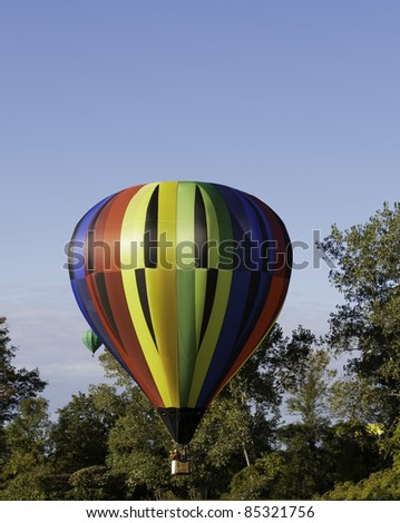 Colorful hot air balloon prepares to land.