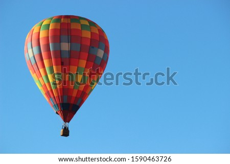 Colorful Hot Air Balloon Sailing in the Bright Blue Sky during the Plano Balloon Festival in Plano, Texas. Image with copy space on the sides.  Foto stock ©