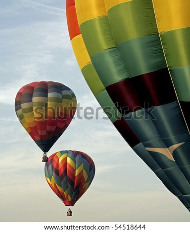 Colorful hot air balloons ascending against a cloud streaked sky.