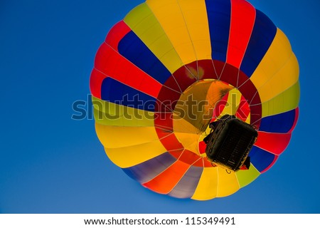 Colorful hot air balloons float up in the blue sky