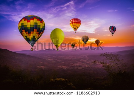 Colorful hot air Balloons  flying above green mountain at sunset time with  beautiful twilight sky background #1186602913