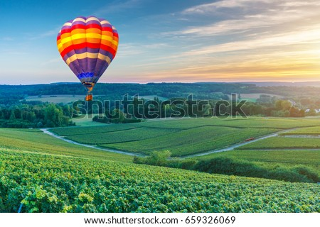 Colorful hot air balloons flying over champagne Vineyards at sunset montagne de Reims, France - Shutterstock ID 659326069