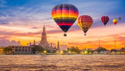 Colorful hot air balloons flying over Chao Phraya River near Wat Arun Temple at twilight in Bangkok, Thailand