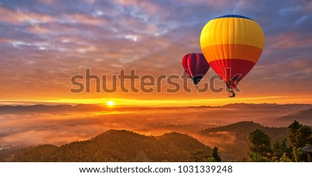 Colorful hot-air balloons flying over misty morning sunrise at Chiang Mai, Thailand. - Shutterstock ID 1031339248
