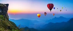 Colorful hot air balloons flying over mountain with sunrise at at phucheefa mountain. Chiang Rai Province, Thailand