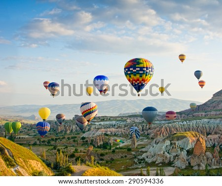 Colorful hot air balloons flying over Red valley at Cappadocia, Anatolia, Turkey. Volcanic mountains in Goreme national park. - Shutterstock ID 290594336
