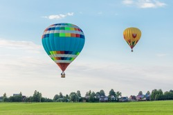 Colorful hot air balloons flying over the countryside in summer