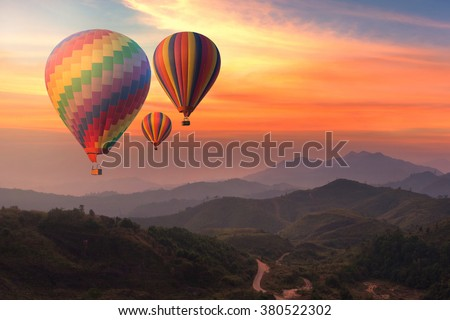 Colorful hot-air balloons flying over the mountain - Shutterstock ID 380522302