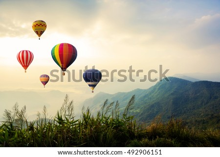 Colorful hot-air balloons flying over the mountain - Shutterstock ID 492906151