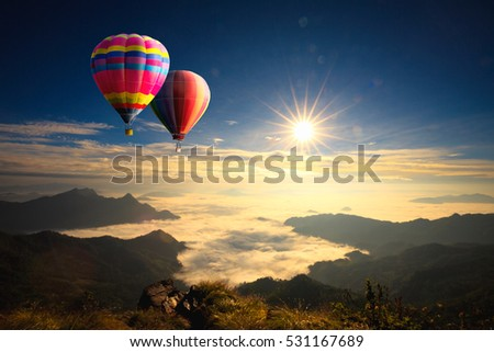 Colorful hot-air balloons flying over the mountain - Shutterstock ID 531167689