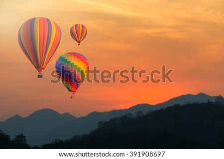 Colorful hot-air balloons flying over the mountain and traveler - Shutterstock ID 391908697