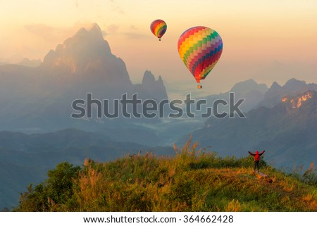 Colorful hot-air balloons flying over the mountain and traveler,travel concept