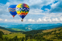 Colorful hot-air balloons flying over the mountains. Artistic picture. Beauty world